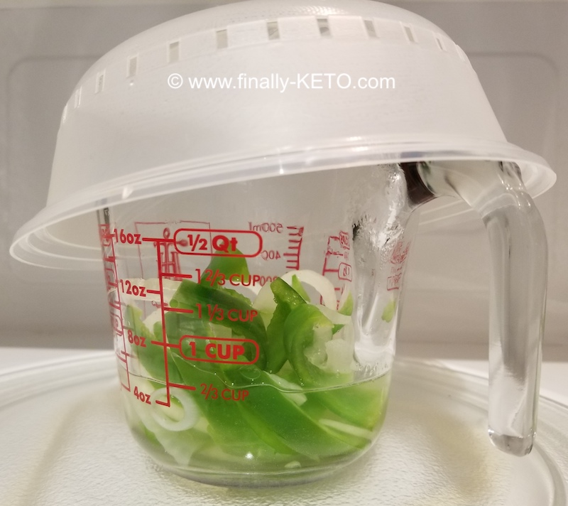 sliced onion and green peppers being microwaved in small amount of water